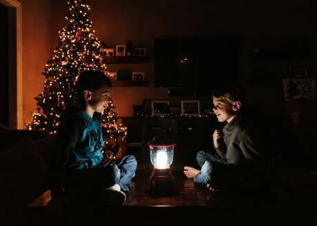 Brothers with illuminated lantern sitting by Christmas tree at home - CAVF14555