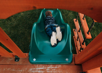High angle view of playful boy sliding at park - CAVF14564
