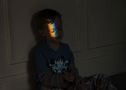 Spectrum falling on boy's face while sitting in darkroom - CAVF14588