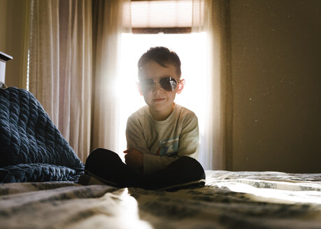 Portrait of boy with arms crossed wearing sunglasses while sitting on bed at home - CAVF14591
