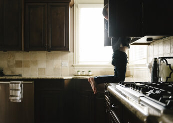 Boy searching something in cabinet while kneeling on kitchen counter at home - CAVF14594