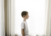Side view of boy standing against curtains at home - CAVF14603