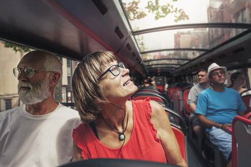 Mature couple travelling in bus on sunny day - CAVF14621