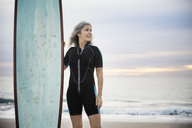 Smiling female surfer looking away while holding surfboard at Delray beach during sunset - CAVF14732