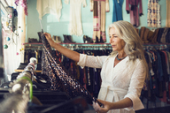 Mature female owner examining dress in clothing store - CAVF14756