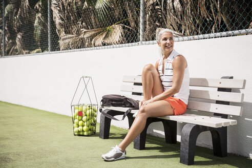 Full length of smiling mature woman sitting at tennis court - CAVF14792
