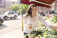 Young woman choosing potted plants at market stall - CAVF14807