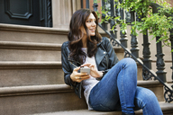 Thoughtful woman holding smart phone while sitting on steps - CAVF14816