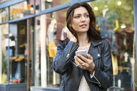 Thoughtful woman holding smart phone outside shop - CAVF14822