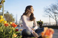 Thoughtful woman sitting on retaining wall with One World Trade Center in background - CAVF14831