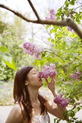 Beautiful woman smelling flowers in park - CAVF15026