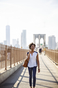 Thoughtful woman walking on footpath with Brooklyn Bridge and One World Trade Center in background - CAVF15035