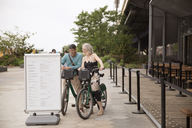 Happy mature couple reading information sign while standing with bicycles on street - CAVF15062