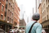 Rear view of man wearing bicycle helmet in city - CAVF15065