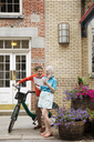 Happy mature couple reading road map while standing with bicycle on sidewalk - CAVF15071
