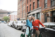 Happy mature couple taking selfie while standing with bicycles on city street - CAVF15074