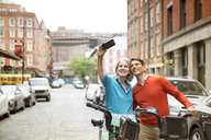 Mature couple taking selfie while standing with bicycles on city street - CAVF15077