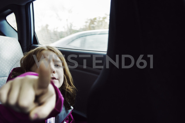 Portrait of girl pointing while sitting by window in car - CAVF15185