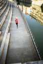 High angle view of sporty woman running on footpath by river - CAVF15227