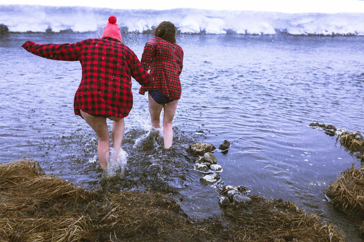 Rear view of female friends enjoying in lake during winter - CAVF15290 - Cavan Images/Westend61