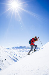 Female hiker climbing snow covered mountain against sky during sunny day - CAVF15329