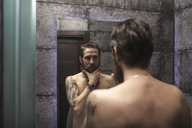 Portrait of bearded man looking at his mirror image - VPIF00388