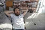 Portrait of bearded man relaxing on the couch at home - VPIF00391