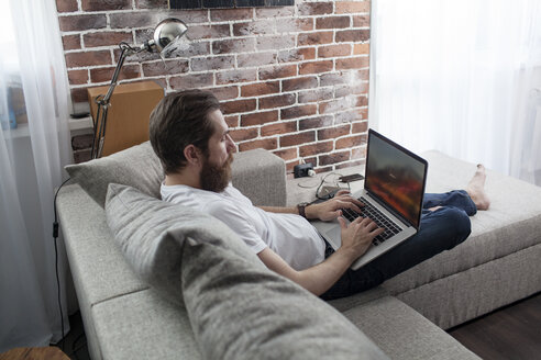 Man sitting on the couch at home using laptop - VPIF00406