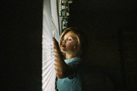 Girl looking though window blinds while standing in darkroom at home - CAVF15382