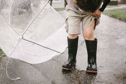 Girl in rubber boots holding umbrella while standing on wet road - CAVF15406