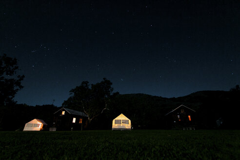 Illuminated tents and houses on field against starry sky at night - CAVF15421