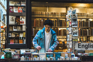 Young man in bookshop - AFV00350