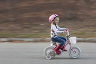 Happy girl riding bicycle on road by field - CAVF15601