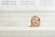 Cheerful girl splashing water while bathing in bathtub at home - CAVF15604