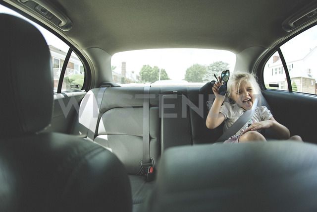 Playful girl with sunglasses sitting in car on sunny day - CAVF15622