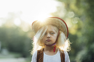 Portrait of girl wearing sun hat standing in park during sunny day - CAVF15628