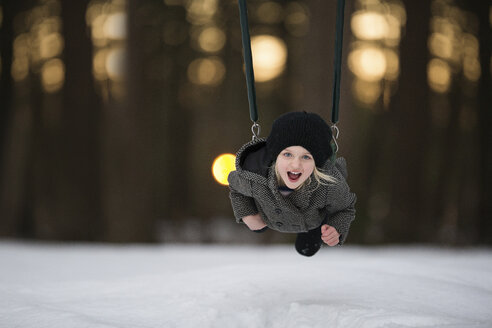 Portrait of cheerful girl playing on swing at snow covered park - CAVF15640