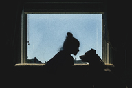 Girl and dog sitting on window sill against clear sky - CAVF15646