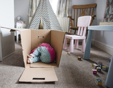 Playful girl relaxing in cardboard box at home - CAVF15661