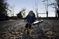 Full length of happy boy playing on sand in playground - CAVF15667