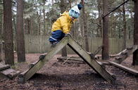 Boy playing on ladder at playground - CAVF15718