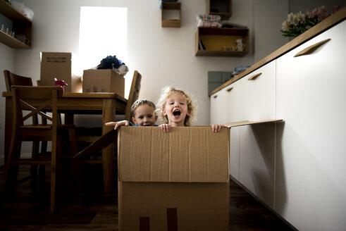 Portrait of cheerful siblings sitting in cardboard box at home - CAVF15754