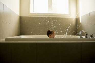 Boy splashing water while taking bath in bathroom - CAVF15787