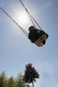 Low angle view of boy swinging against blue sky during sunny day - CAVF15796