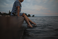 Low section of girl sitting on pier during sunset - CAVF15829