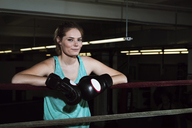 Portrait of smiling sportswoman standing in boxing ring at gym - CAVF15877