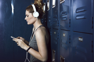 Young woman listening music through phone while standing against lockers - CAVF15883