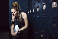 Tired sportswoman listening music while sitting against lockers in gym - CAVF15886