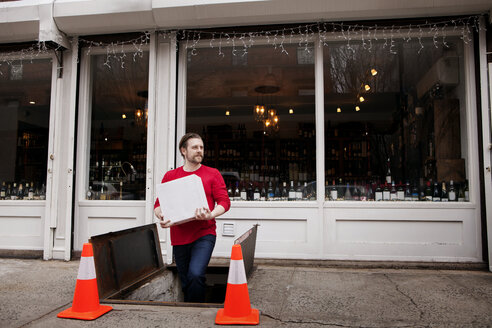 Small Business Owner holding package while exiting underground storehouse outside wine shop - CAVF15892