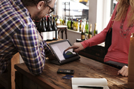 Midsection of female customer using tablet computer while paying at wine shop - CAVF15898